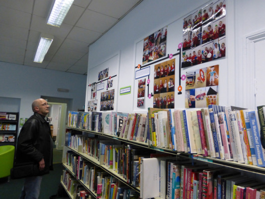 Trevor Avery looking at the exhibition of photographs from the project in Windermere Library
